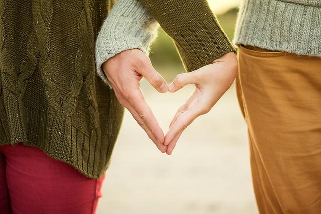 Мужчина и женщина в недорогой цветной одежде держатся за руки
