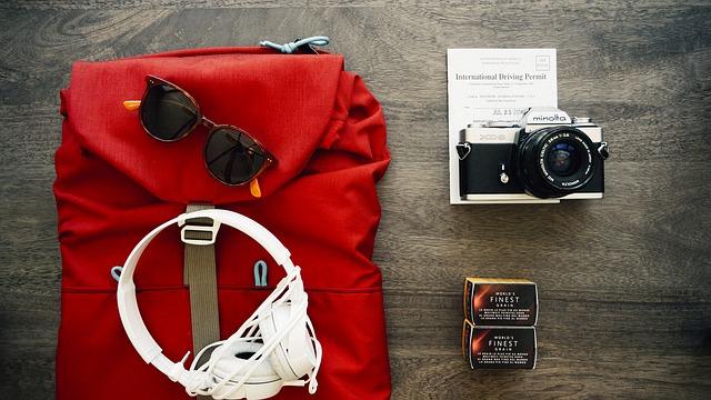 Фотоаппарат, солнечные очки и наушники на столе