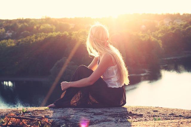 Девушка смотрит на восход солнца, сидя на берегу реки
