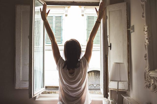 Девушка потягивается возле открытого окна утром