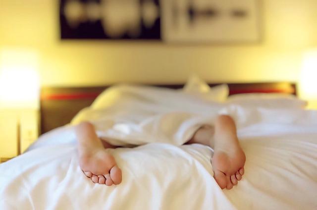 Ноги человека, который без сил упал на кровать