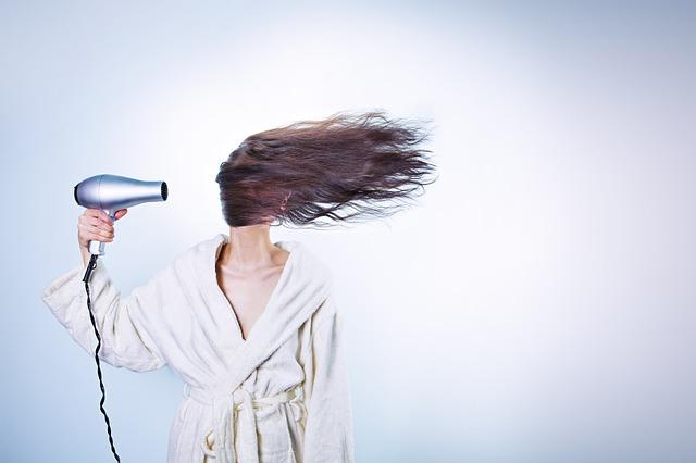 Сонная женщина сушит волосы феном