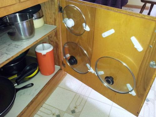 Крышки для кастрюль прикреплены на внутреннюю поверхность дверцы кухонного шкафчика с помощью самоклеящихся крючков для полотенец