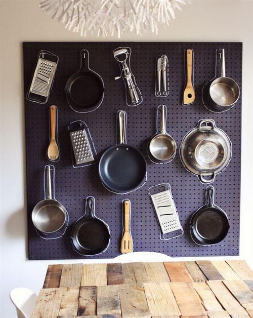 Терка, кастрюля, сковорода и другая посуда висит на одной из стен кухни для экономии пространства