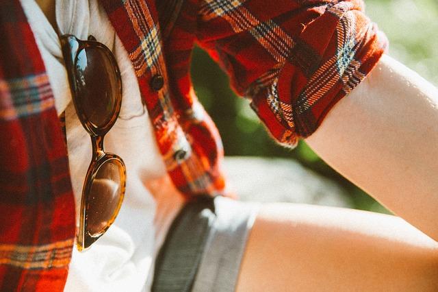 Девушка в клетчатой рубашке, шортах и с солнечных очками