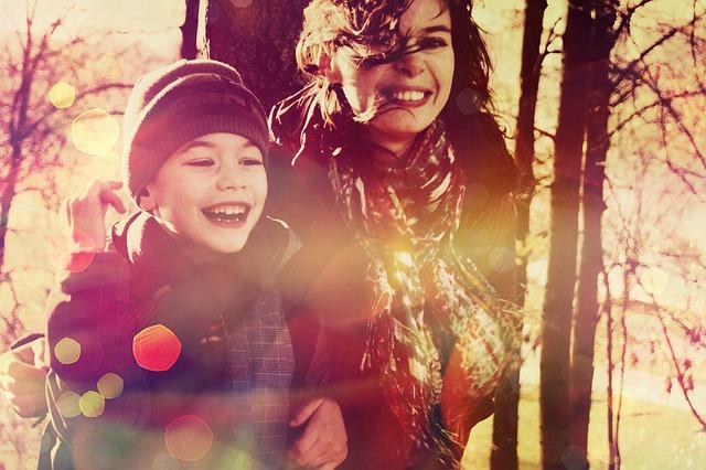 Мама с маленьким сыном смеются на прогулке