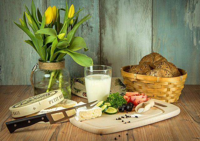 Ваза с тюльпанами, овощи, сыр и хлеб на столе