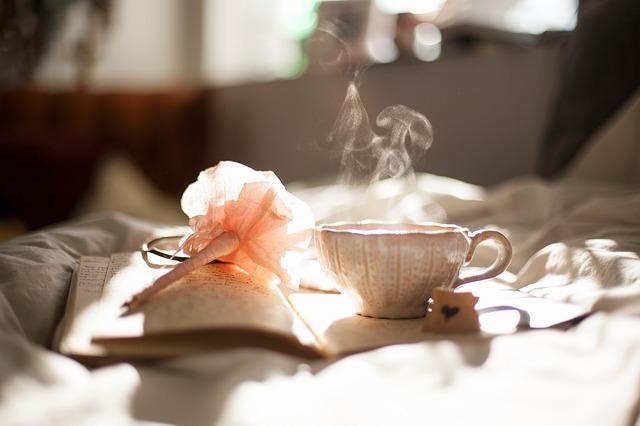 Блокнот и чашка чая на кровати