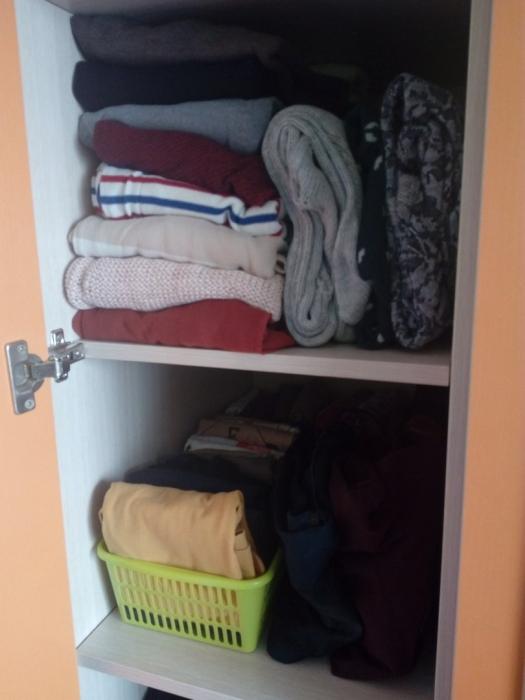Одежда аккуратно сложена в шкафу после расхламления