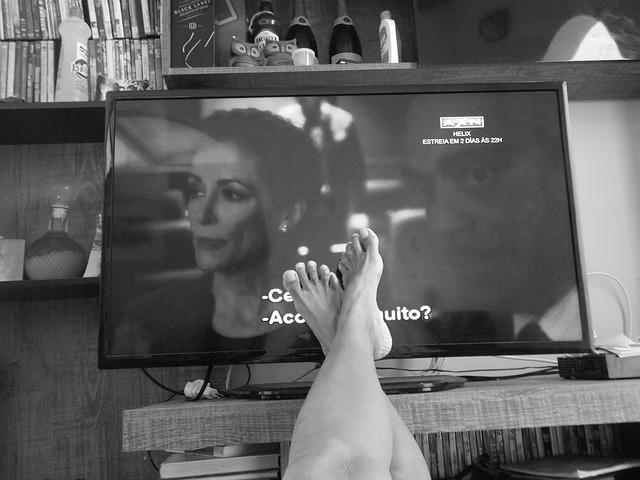 Ноги человека, который лежит перед телевизором