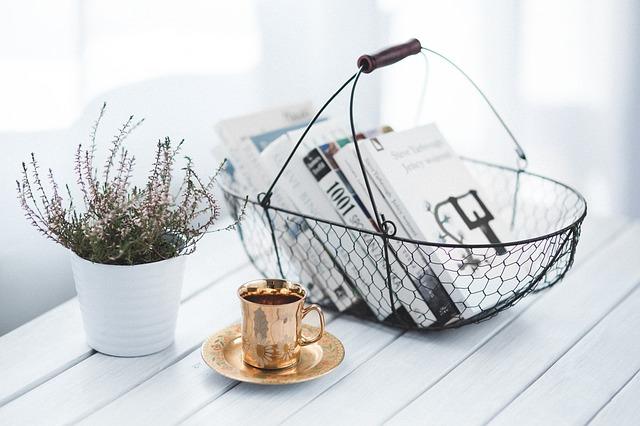 Подставка для книг, цветок и чашка на столе