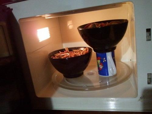 В микроволновке одна из двух тарелок греется на кружке, потому что обе тарелки одновременно рядом не помещаются