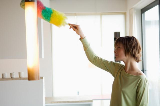 Девушка снимает пыль пушистой щеткой для пыли, которая поможет полюбить уборку