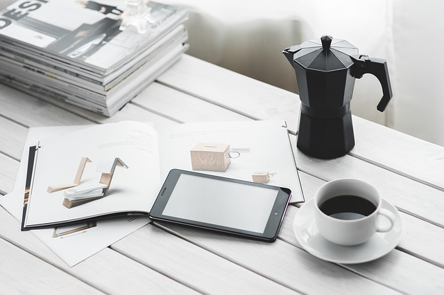 Планшет, кофе и журналы на столе